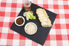 Cream of smoked salmon pate. Cream of salmon pate on a slate plate with pickle and sliced baguette Stock Images