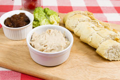 Cream of smoked salmon pate. Cream of salmon pate on a wooden board with pickle and sliced baguette Stock Photo