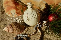Cream snowman decoration on beach sand rock backdrop  shell natural african beads red ball Christmas in July. Off-white snowman on the beach sea sand, marble Stock Photo