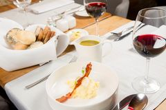 Cream of sorrel and green vegetables soup. With quail egg, sour cream, mashed potatoes and crispy bacon served in a jug in a restaurant Stock Images