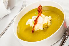 Cream of sorrel and green vegetables soup. With quail egg, sour cream, mashed potatoes and crispy bacon served in a restaurant Royalty Free Stock Images