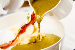 Cream of sorrel and green vegetables soup. With quail egg, sour cream, mashed potatoes and crispy bacon being poured from a jug Royalty Free Stock Photo