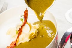 Cream of sorrel and green vegetables soup. With quail egg, sour cream, mashed potatoes and crispy bacon being poured from a jug Royalty Free Stock Image