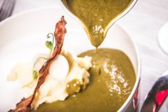 Cream of sorrel and green vegetables soup. With quail egg, sour cream, mashed potatoes and crispy bacon being poured from a jug royalty free stock images