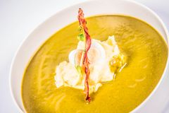 Cream of sorrel and green vegetables soup. With quail egg, sour cream, mashed potatoes and crispy bacon on a white background Stock Photos