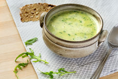 Cream soup from arugula in a rustic bowl, some leaves, spoon an. Green soup from arugula with cream in a rustic bowl, some leaves as garnish, spoon and bread stock images