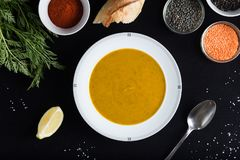 Cream soup of assorted lentil. Yellow and green lens, spices as raw for meal and lemon on black backgraund. Healthy Royalty Free Stock Photos