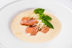 Cream soup with basil, meat steak and cheese on plate. Royalty Free Stock Image