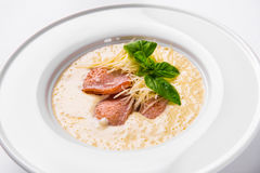 Cream soup with basil, meat steak and cheese on plate. Stock Photography