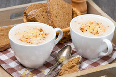 Cream soup of cauliflower with cheese and pepper on a tray Royalty Free Stock Photos