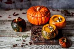 Cream Soup in Hollowed Pumpkins. Pumpkin Cream Soup in Hollowed Pumpkin Bowls, copy space for your text Stock Photos