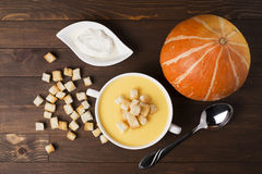 Cream soup of pumpkin with spices, with cream, crackers, on a br. Own wooden table Stock Photo