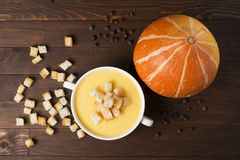 Cream soup of pumpkin with spices, with cream, crackers, on a br. Own wooden table Royalty Free Stock Images