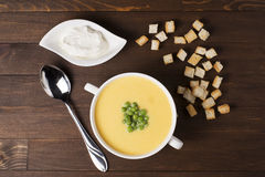 Cream soup of pumpkin with spices, with cream, croutons and peas. On a brown wooden table Royalty Free Stock Photo