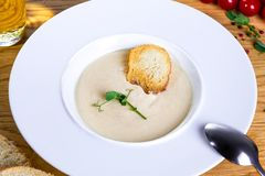 Cream soup served in white plate on wooden background. Delicious porridge, mushroom, potato, cheese cream soup with rusk royalty free stock image