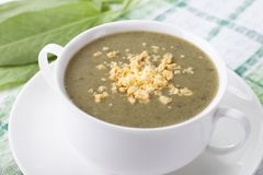 Cream soup from sorrel with yolk. In a white cup Stock Photos