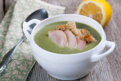 Cream soup with spinach and croutons. On a wooden board Royalty Free Stock Photo