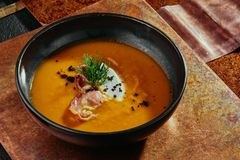 Cream soup of sweet potato with truffle, cheese and bacon in a black plate on a copper background. stock images
