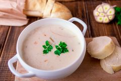 Cream soup in white bowl near bread on wooden background. Rustic style Royalty Free Stock Photography
