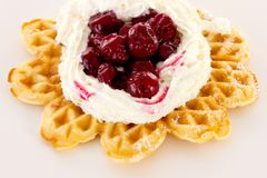 Cream and sour cherries on fresh baked waffle Royalty Free Stock Photos