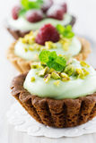 Cream tarts with nuts, raspberry and mint. Mini tarts with pistachio cream, raspberry and fresh peppermint leaves Royalty Free Stock Photo