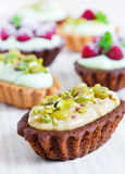 Cream tarts with pistachio nuts. Raspberry and mint Royalty Free Stock Photos