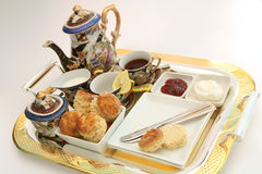 Cream tea 1. A gilt-edge tray with an English cream tea, featuring scones, cream, strawberry jam and tea, with a Chinese tea set Royalty Free Stock Images