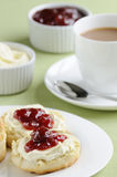Cream tea. Traditional English cream tea of scones, clotted cream, strawberry jam and a cup of tea. These are served Devonshire style, with the jam on top Royalty Free Stock Photography