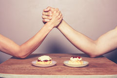 Cream tea rivalry. Two people are arm wrestling to decide on the best way of preparing a cream tea Royalty Free Stock Photo