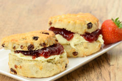 Cream tea scones - ready to eat. Two cream tea scones with clotted cream and strawberry jam - studio shot with a shallow depth of field Royalty Free Stock Photo