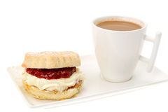 Cream tea, scones with strawberry jam. Cream tea - scones with strawberry jam and whipped cream and a cup of coffee - studio shot with a white background Royalty Free Stock Image