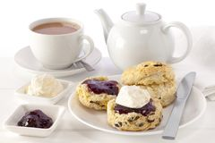 Cream Tea with Teapot. Cream Tea - scones with jam and cream, served with a cup of tea Royalty Free Stock Image