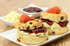 Cream teas - ready to eat. Two cream tea scones with clotted cream and strawberry jam with side dishes of extra jam and clotted cream - studio shot with a Royalty Free Stock Photography