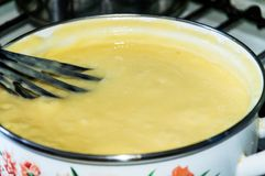 Preparation of custard for a cake Napoleon. Cream. The thickened cream gets mixed thoroughly with butter till homogeneous Royalty Free Stock Photos