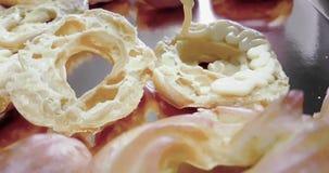 Женщина подготавливает очень вкусные cream вызванные десерты zeppole St Joseph в лотке выпечки с saccapoche, итальянское традицио