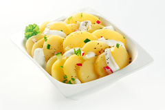 Creamed Boiled german Potato salad on White Bowl. Close up Creamed german Potato salad Slices on White Bowl with Spices and Herbs. Isolated on White Background royalty free stock photos