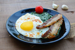 Creamed spinach with fried egg and bacon Stock Photo