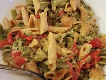 Creamy Alfredo pasta. Creamy warm delicious Alfredo penne pasta tossed with roasted read pepper broccoli and herbs stock image