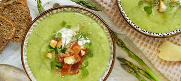 Creamy asparagus and potatoes soup puree. On a wooden table royalty free stock images