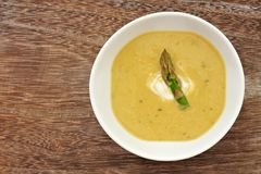 Creamy asparagus soup overhead view on rustic wood Stock Photos