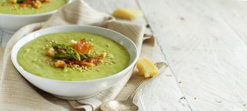 Creamy asparagus soup. Creamy asparagus and potatoes soup puree on a wooden table royalty free stock image