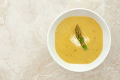 Creamy asparagus soup in white bowl on white granite Royalty Free Stock Photography