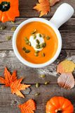 Creamy autumn butternut squash soup on rustic wood background Royalty Free Stock Image