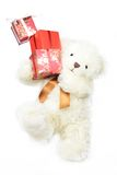 Creamy bear keeping gifts. Balancing on the one leg Stock Photos