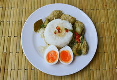 Creamy boiled egg yolk and spicy fish ball green curry on rice. Creamy boiled egg yolk and spicy fish ball green curry on plain rice Stock Image