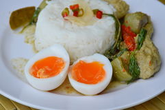 Creamy boiled egg yolk and spicy fish ball green curry on rice. Creamy boiled egg yolk and spicy fish ball green curry on plain rice Stock Photo