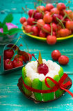 Creamy cake with cherries. Wooden turquoise background. Top view. Close-up Stock Images