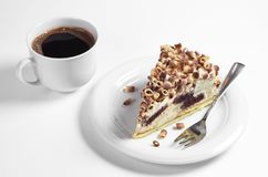 Creamy cake and coffee. Slice of creamy cake decorated chocolate chips in plate and cup of coffee on white background Stock Photography