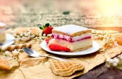 Creamy cake with strawberry on plate. On rustic table Royalty Free Stock Photography