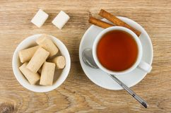 Creamy candy bars in bowl, tea, cinnamon, sugar and teaspoon. Creamy candy bars in bowl, cup of tea, cinnamon, sugar and teaspoon on wooden table. Top view Stock Image